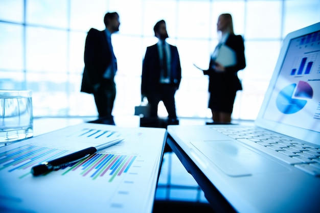 Close-up of a financial report with businesspeople background Free Photo