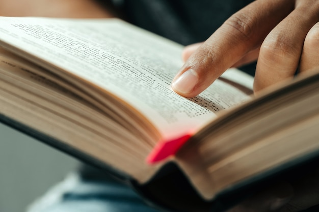 Close-up of finger pointing text in bible.close up of man reading through the bible. Premium Photo