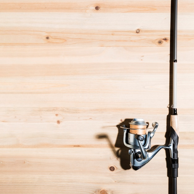Close-up of fishing rod on wooden desk Free Photo