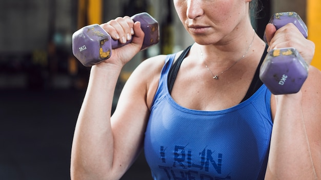 Close-up of a fit woman exercising with dumbbells Free Photo
