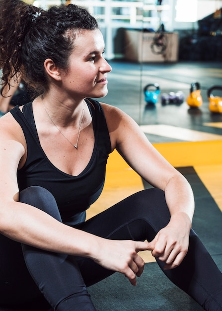 Close-up of a fit young woman sitting on floor in gym Free Photo