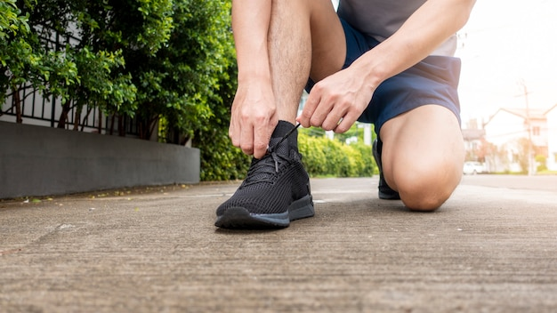 Close up of fitness man is tie shoes Premium Photo