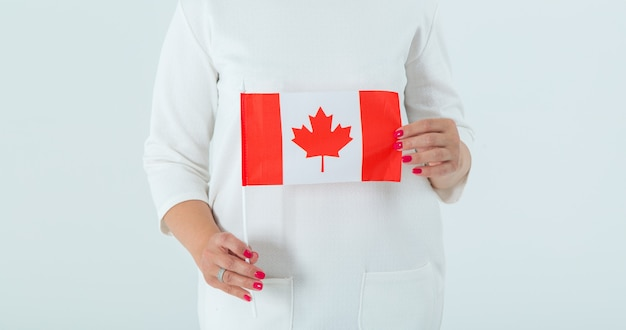 Close-up of the flag of canada in female hands. Premium Photo