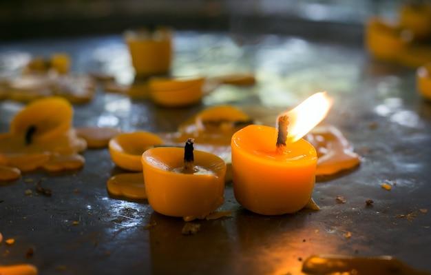 Закройте пламя воска в храме для зажигания и молитвы Premium Фотографии