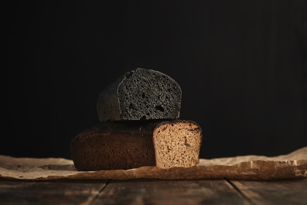 2つの焼きたてのダイエット健康パンに焦点を当てます。素朴な木製のテーブルに提示された黒で分離されたイチジクと木炭とライ麦 無料写真