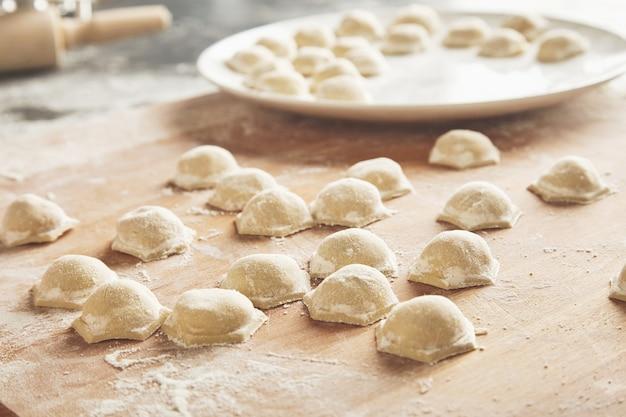 Close up focus pronti gustosi ravioli o gnocchi ripieni di carne macinata sulla farina sulla tavola di legno Foto Gratuite