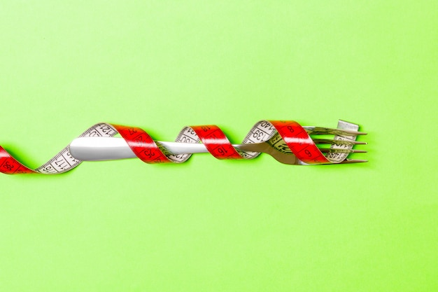 Close up of fork wrapped with tape measure on green Premium Photo