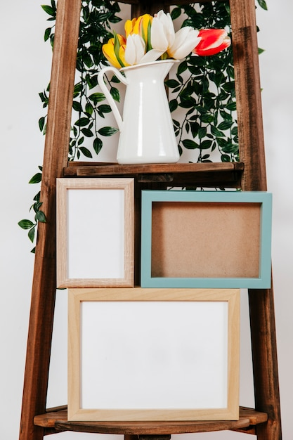 Close-up frames and flowers on shelf Free Photo