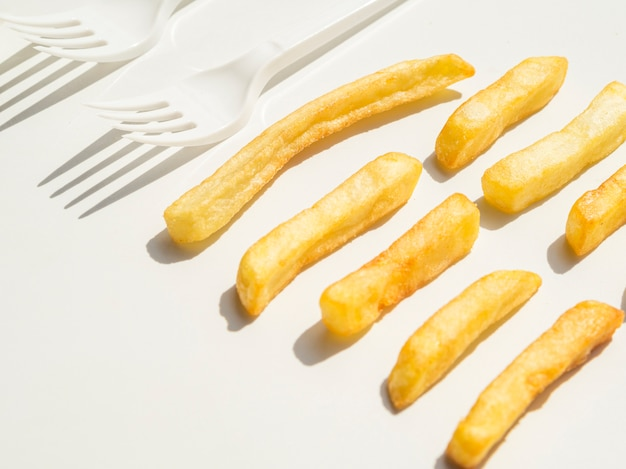 Close-up of french fries and forks Free Photo