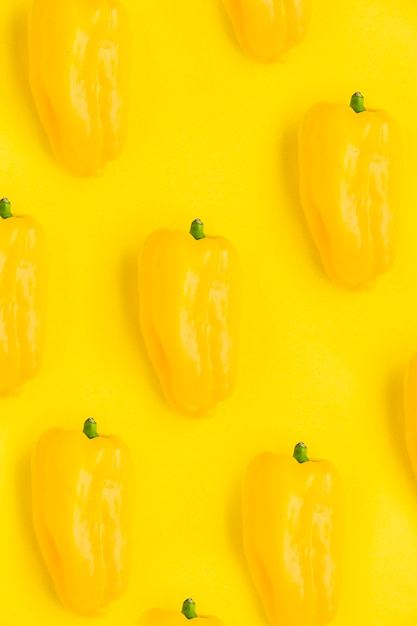 Close-up of fresh bell peppers on yellow backdrop Free Photo