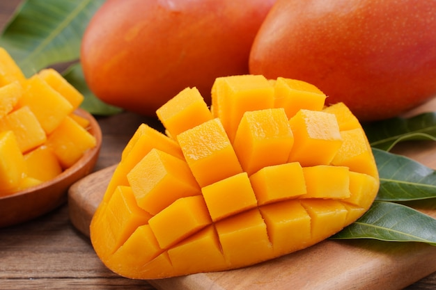 Close up of fresh chopped mango with green leaves Premium Photo