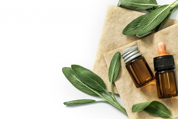 Close up fresh green sage herb leaf with a bottle of essential oil on white background , herb essence Premium Photo