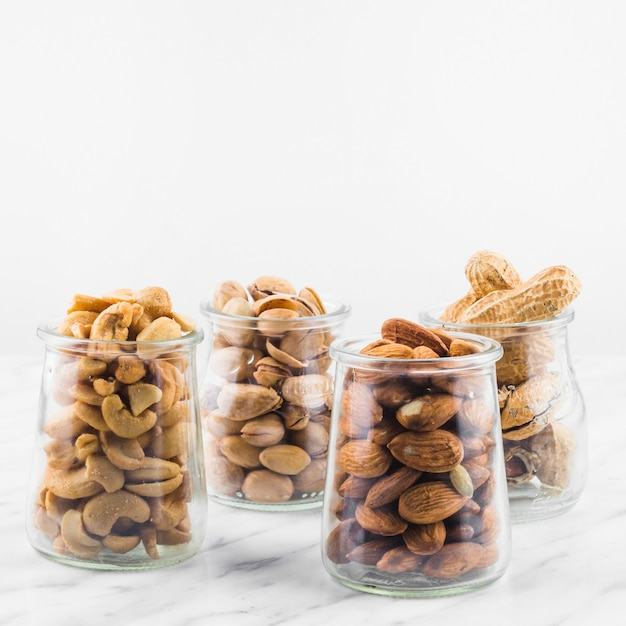 Close-up of fresh nut food in jar on marble surface Free Photo
