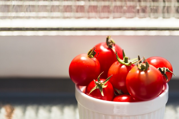 Close-up of fresh red cherry tomatoes in container Free Photo