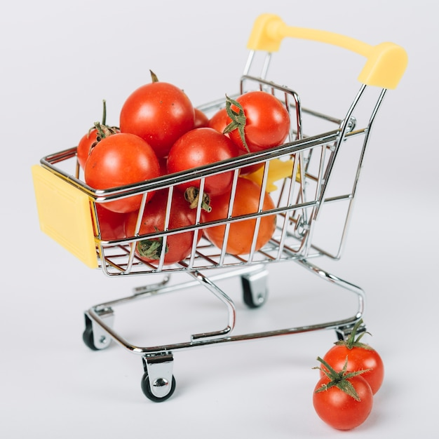 Close-up of fresh tomatoes in trolley on white surface Free Photo