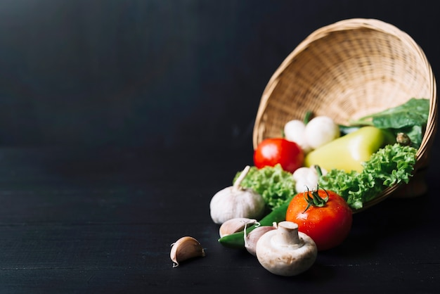 Close-up of fresh vegetables with wicker basket on black wooden backdrop Free Photo