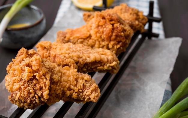 Close-up di ali di pollo fritte sul vassoio con cipolle verdi Foto Gratuite
