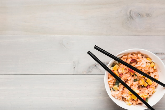 Close-up of fried rice bowl with black chopsticks on table Free Photo
