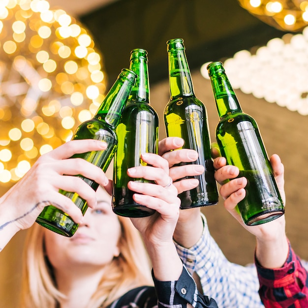 Close-up of friend's hands clinking the beer bottles Free Photo