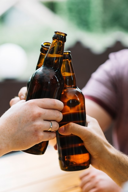 Close-up of friends clinking with brown bottles Free Photo