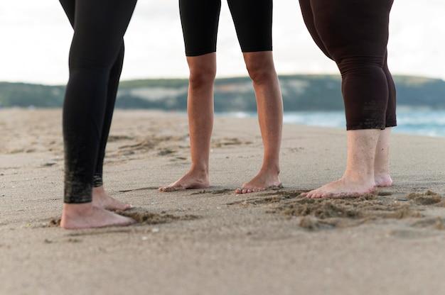 Close-up friends feet on sand Free Photo