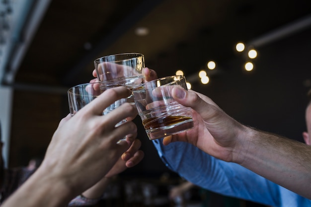Close-up of friends hand raising toast with glass of whiskey Free Photo