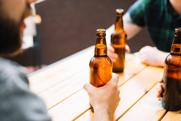 Close-up of friends holding beer bottles on wooden table Free Photo