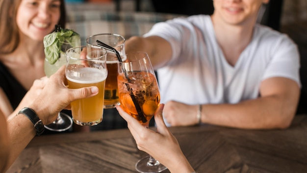 Close-up of friends toasting drinks Free Photo
