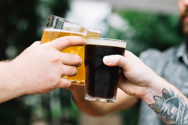 Close-up of friends toasting glass of drinks Free Photo