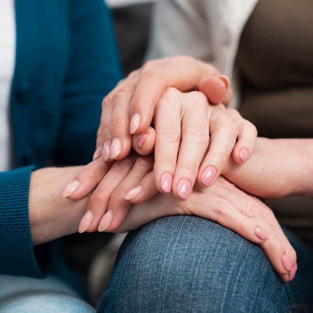 Close-up friends touching hands Free Photo