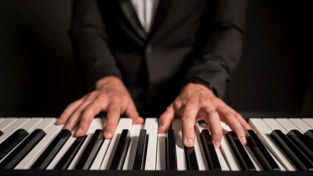 Close-up front view professional keyboard player Free Photo