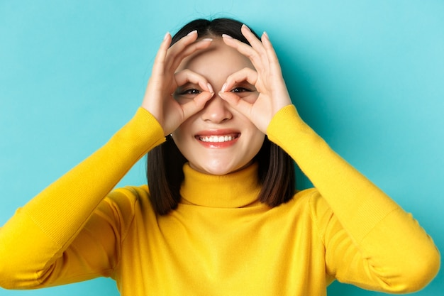 Close up of funny asian girl looking through hand glasses and smiling, checking out promo offer, standing over blue background. Premium Photo