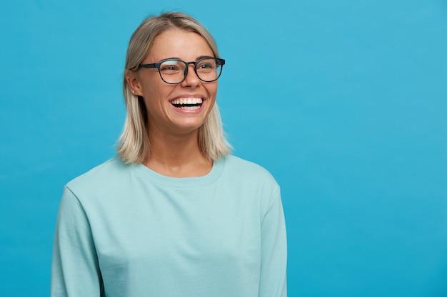 Chiuda in su della giovane donna bionda felice allegra divertente in vetri con il sorriso a trentadue denti Foto Gratuite