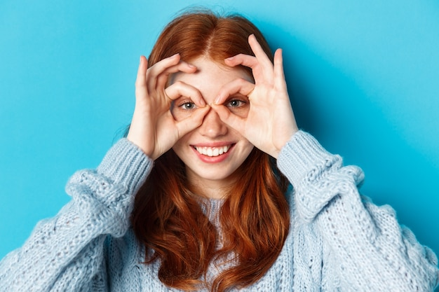 Close-up of funny and cute redhead girl making hand glasses and looking through them, seeing promo offer and smiling, standing over blue background. Premium Photo