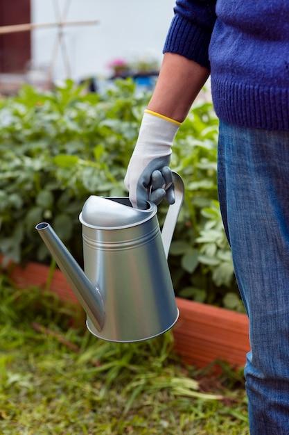 Крупный план садовника, держа спринклер в саду Бесплатные Фотографии