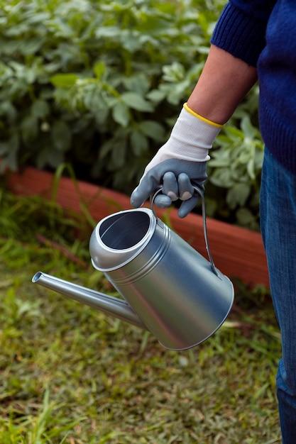 Крупный план садовника с разбрызгивателем Бесплатные Фотографии