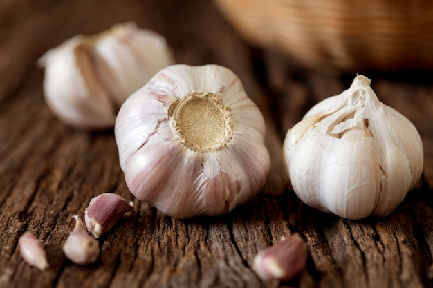Close up a garlic bulb in bowl on wooden table Premium Photo