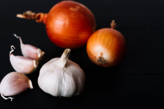 Close-up of garlic bulb and onions on black background Free Photo