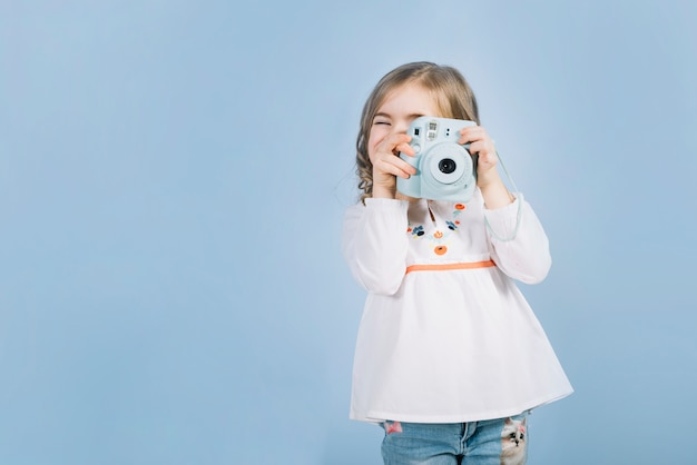 Close-up of a girl capturing the photo with instant camera against blue backdrop Premium Photo