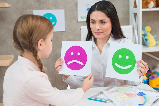 Close-up of a girl choosing sad face emoticons paper held by smiling young psychologist Free Photo