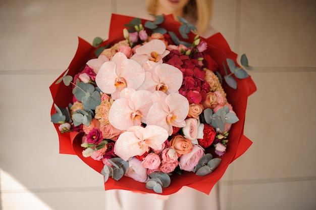 Close up girl in the coat holding a bouquet of pink and red flowers decorated with greenery Premium Photo