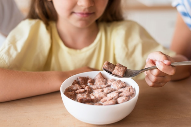 Close-up girl eating milk and cereals Free Photo