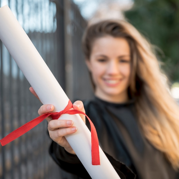 Close-up girl at her graduation holding certificate Free Photo