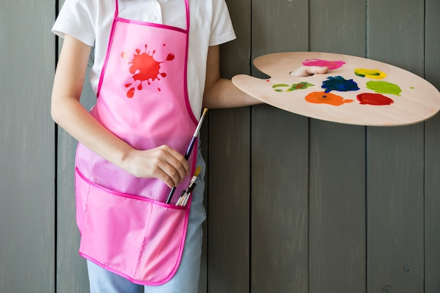 Close-up of a girl holding palette in hand removing the paint brush from pink apron standing against grey wooden wall Free Photo