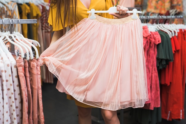 Close-up girl holding a pink skirt Free Photo