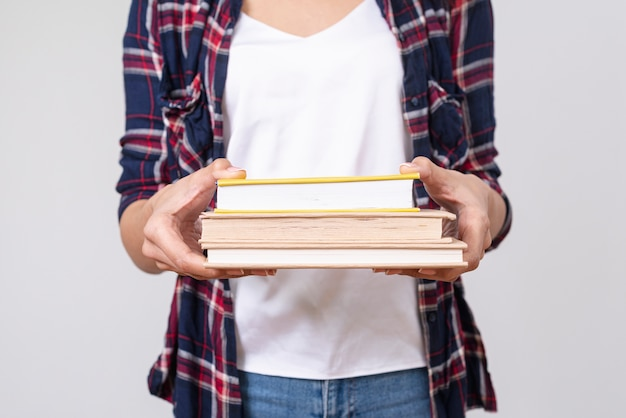 Close-up girl holding stack of books Free Photo