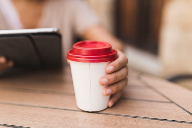 Close-up of a girl holding takeaway coffee cup on table Free Photo
