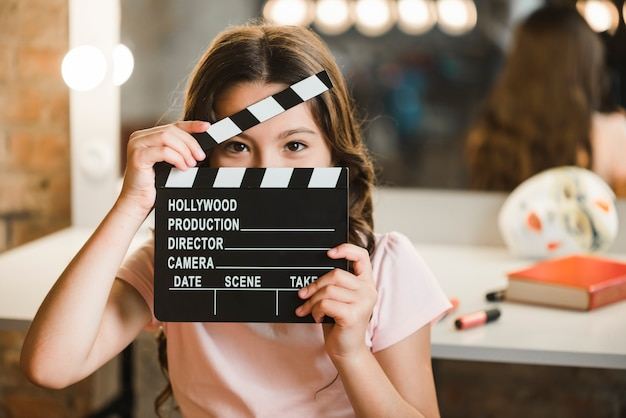 Close-up of girl looking through clapper board Free Photo