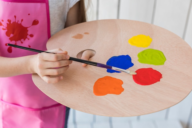Close-up of a girl mixing the paint with brush on wooden palette Free Photo
