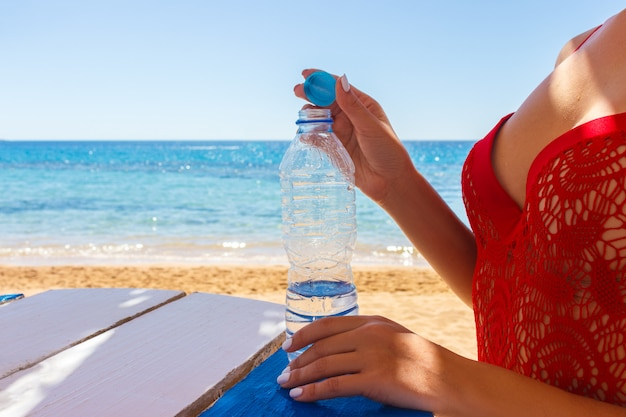 Close-up of a girl opening a plastic water bottle after swimming in the sea Premium Photo